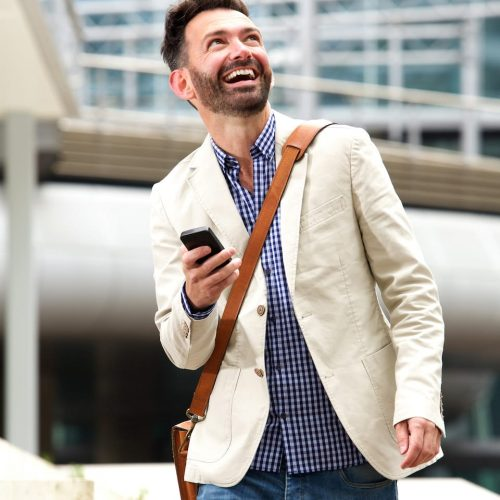smiling-mature-man-outdoors-with-mobile-phone-PB28ME5
